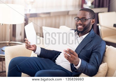 Time to deal with it. Cheerful lucky afro American businessman in suit looking at some documents while sitting on the sofa
