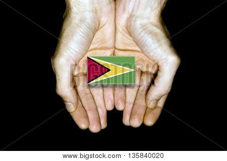 Flag Of Guyana In Hands On Black Background