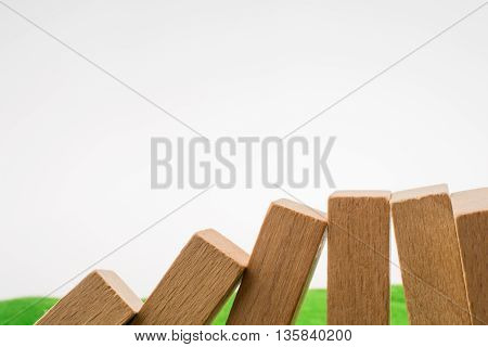 Wooden domino pieces  placed on green grass