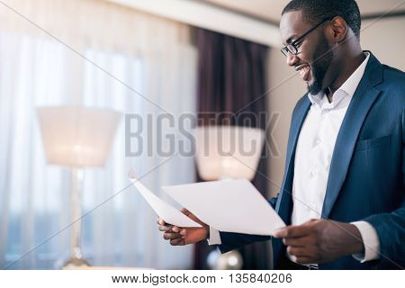 Good results. Profile of a contented energetic young afro American man standing and holding documents while looking at them with satisfaction