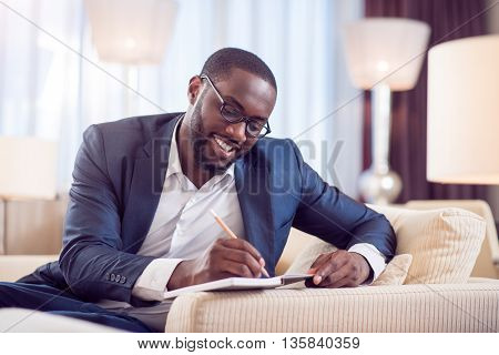 Lets work. Satisfied young afro American man in suit while taking notes in a diary while sitting on the sofa in a hotel