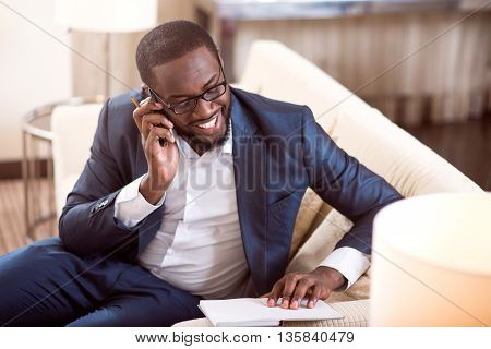 Fixing a meeting. Contented confident mature afro American professional talking on the phone and checking information in his notebook
