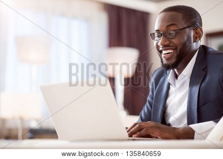I can not believe. Surprised satisfied afro American man with glasses looking at the screen of his laptop while sitting