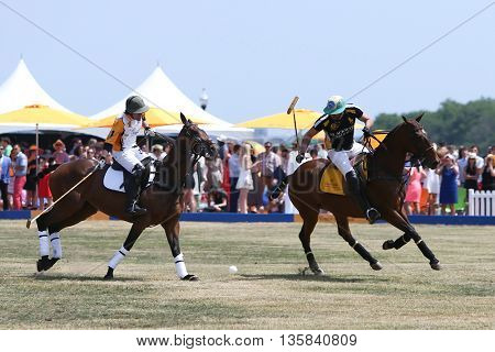 JERSEY CITY, NJ-MAY 30: Rico Mansur (R) handles the ball as Edward Hartman gives chase at the 8th Annual Veuve Clicquot Polo Classic at Liberty State Park on May 30, 2015 in Jersey City, NJ.