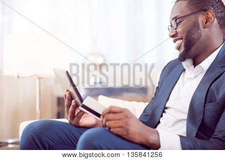 Lets see. Profile of a mature contented afro American man in suit holding a bank card while looking at the tablet and sitting on the couch