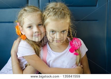 Two girls hugging look in the frame sitting in an electric train close-up