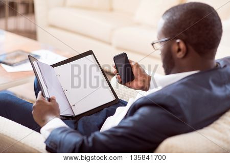 Involved in work. Back view of a calm thoughtful afro American man sitting on the couch and looking at an open folder while holding smart phone