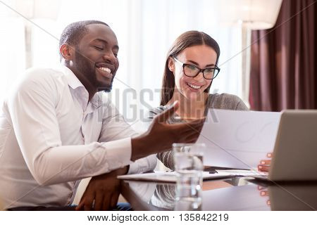 It is a success. Beautiful woman and contented afro American man looking at the papers and rejoicing the success of their work