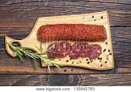 Salami sausages sliced on cutting board on table top view