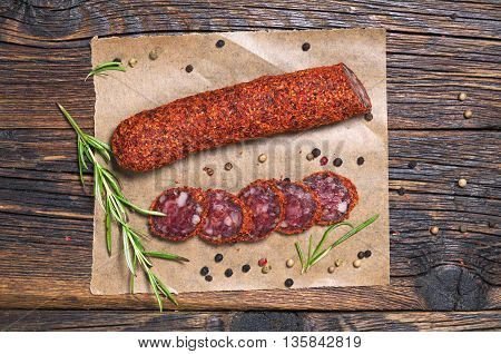 Salami sausages sliced on paper on a wooden table top view