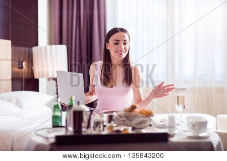 Good morning. Beautiful pretty woman holding a laptop while sitting on the bed and looking a tray with a breakfast