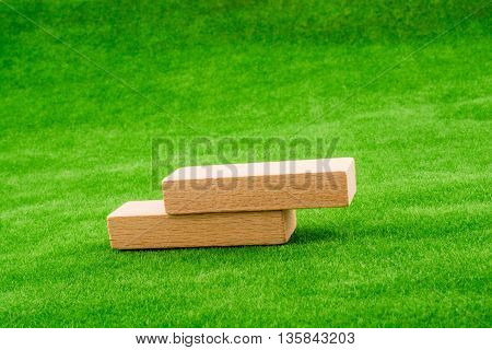 Wooden domino pieces olaced on green grass