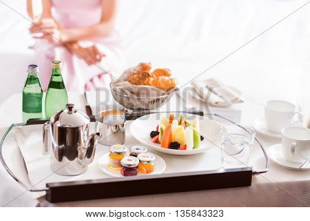 I want to eat it all. Close up of a tray with delicious fruit salad and tea for breakfast with a woman sitting on the bed on the background