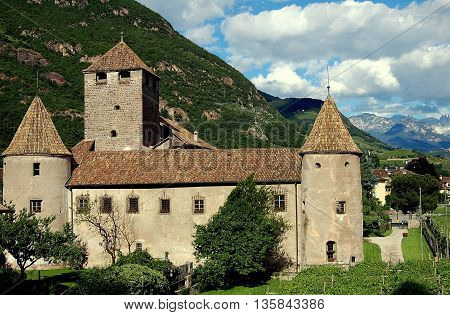 Bolzano Italy - June 2 2006: The feudal Castello Mareccio with ienclosure defensive wall round towers capped with conical roofs and giant keep surrounded by Tyrolean vineyards and the nearby Dolomite Mountains