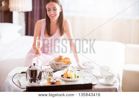 Excellent service. Close up of a tray with a breakfast with a beautiful woman drinking champagne on the background