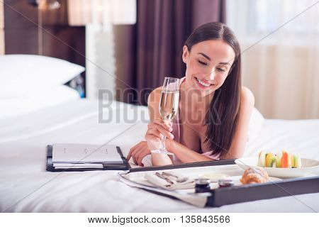 Feeling relaxed. Beautiful relaxed woman drinking champagne while lying on the bed in the hotel and looking at the tray with food