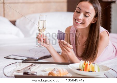 So good. Cheerful young woman looking at the business card while lying on the bed near a tray and holding a wineglass