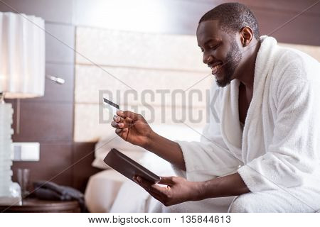 It is comfortable. Contented handsome afro American man wearing a bathrobe holding a bank card and looking at the screen of a tablet while sitting on the bed in a hotel