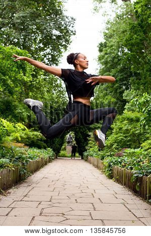 a jazz dancer in mid air outdoors