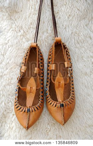 Pair of traditional Bulgarian leather shoes agaisnt white lambskin background