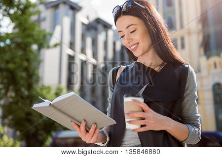 Full of joy. Positive smiling beautiful glad woman reading book and drinking coffee while standing in the street