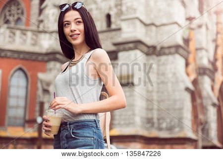 Refresh your mind. Pleasant delighted charming woman holding coffee and resting while having a walk