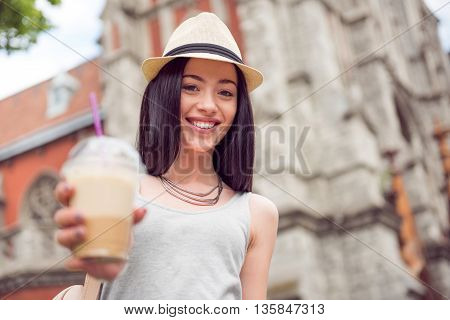 Help yourself. Cheerful delighted beautiful woman holding coffee and giving it to you while having a walk
