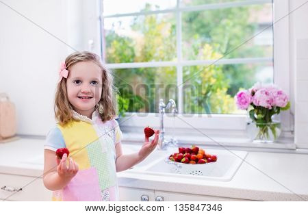 Cute little girl washing fruit in kitchen sink. Child eating strawberry. Kids wash strawberries. Fresh berry for family snack. Healthy nutrition for children. Preschooler kid making breakfast.