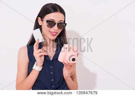 Full of gladness. Cheerful content beautiful smiling woman holding photo and camera while standing isolated on white background