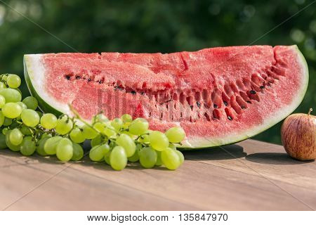 Some juicy red watermelon on a wooden table, outdoors