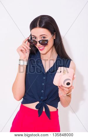 Playful mood. Cheerful delighted smiling woman wearing glasses and holding photo camera while expressing positivity