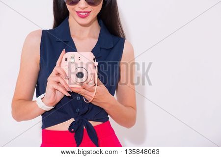 Just smile. Positive delighted beautiful woman holding photo camera and expressing gladness while standing isolated on white background