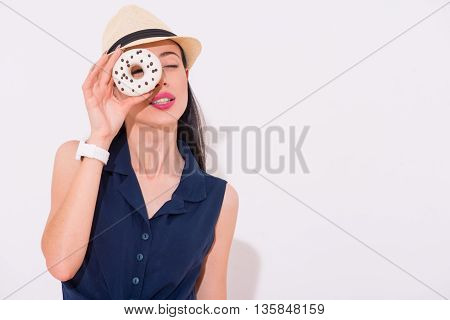 Sweet days. Cheerful delighted beautiful woman holding donut and going to eat it while feeling glad