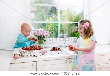 Little girl and baby boy washing fruit in kitchen sink. Children eat strawberry. Kids wash strawberries. Fresh berry for family snack. Healthy nutrition for child. Preschooler kid making breakfast.