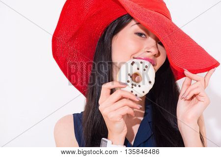 Taste it. Pleasant delighted magnetic woman holding donut and going to eat it while seducing you