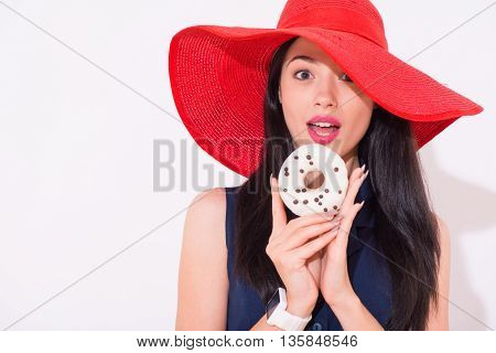 Magic taste. Portrait of delighted beautiful woman holding donut and going to eat it while standing isolated on white background