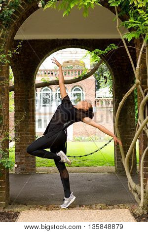 a jazz dancer performing under an archway