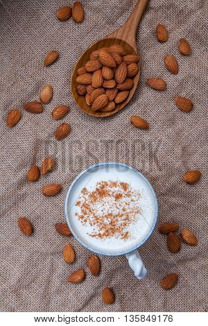 Homemade Almond Milk In Cup With Whole Almonds In Wooden Spoon On Hemp Sack Background .