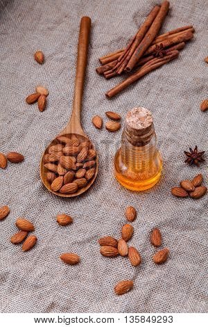 Bottle Of Extra Virgin Almonds Oil With Whole Almonds And Cinnamon Sticks On Hemp Sack Background.