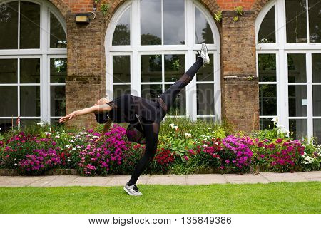 A jazz dancer performing a kick outdoors.