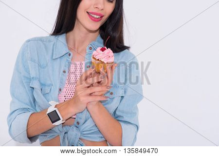 Nice dessert. Close up of cupcake in hands of pleasant delighted beautiful woman holding it and going to eat while expressing joy