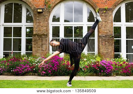 A young jazz dancer performing jazz moves outdoors