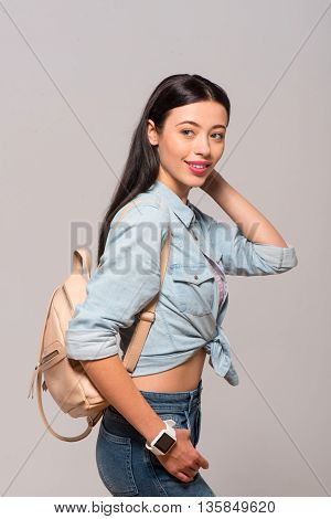 In a good mood. Cheerful delighted beautiful woman wearing bag and looking aside while standing isolated on grey background