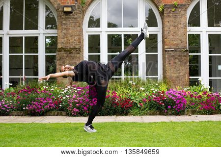 A jazz dancer perming a kick outdoors