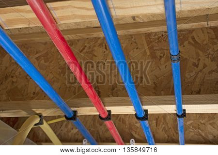 PEX and drain pipes attached to the basement ceiling of a home angled view.
