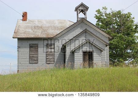 Old abandoned school house on grassy hill