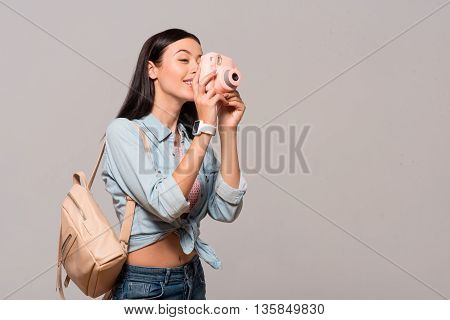 Say cheese. Positive delighted smiling woman holding photo camera and making shots while expressing gladness