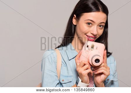 Pleasant day. Portrait of nice delighted beautiful woman holding photo camera and smiling while standing isolated on grey background