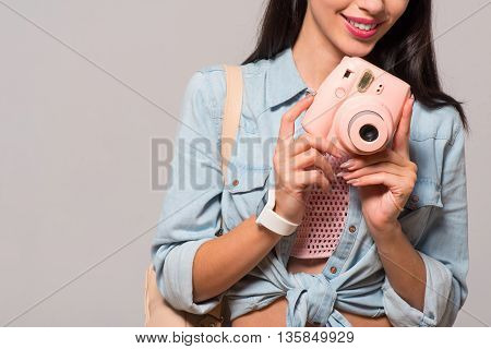 On the edge of positivity. Cheerful pleasant content woman holding photo camera and smiling while standing isolated on grey background