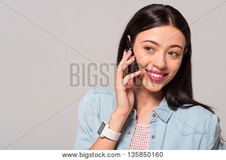 Nice to hear you. Cheerful delighted smiling woman talking on cell phone and expressing joy while standing isolated on grey background